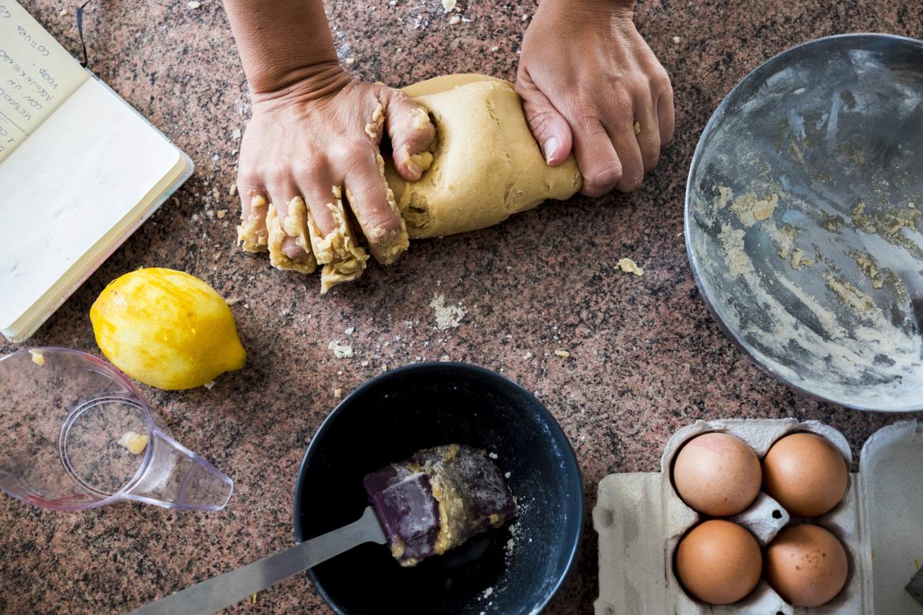 A pair of woman strong hands doing pasta for a cake in the kitchen. Eggs and lemon. Taken from above with different point of view