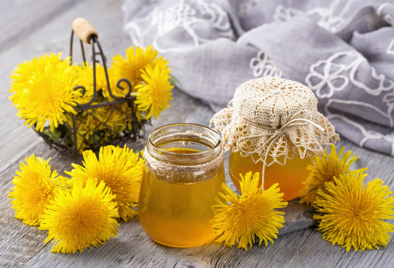 Dandelion jam or honey in a jar and fresh flowers